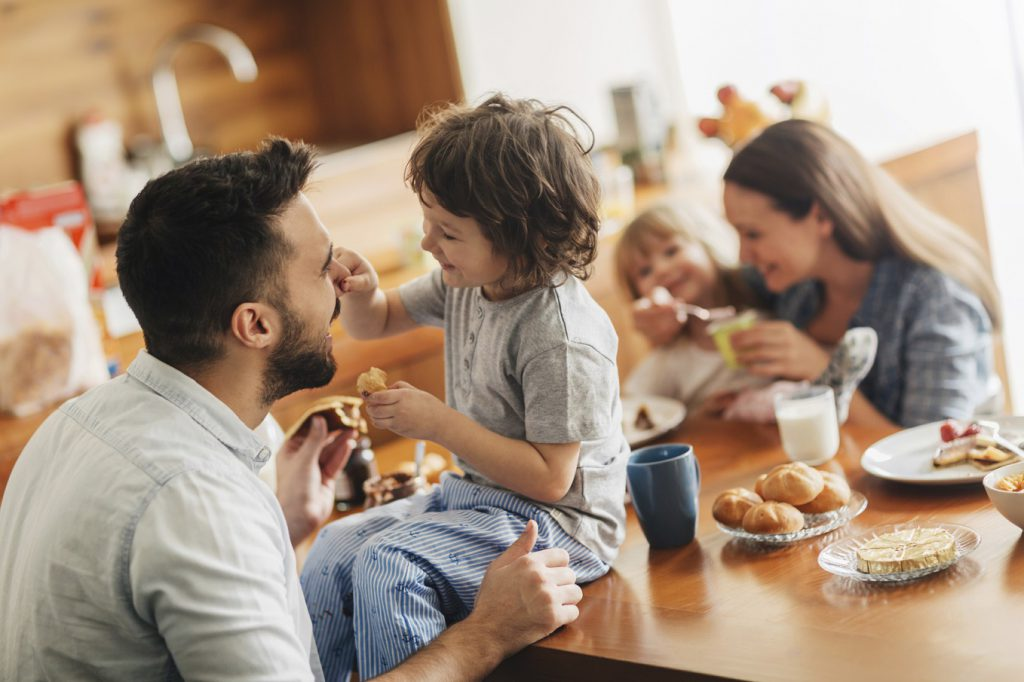 Picture of a young happy family having breakfast together