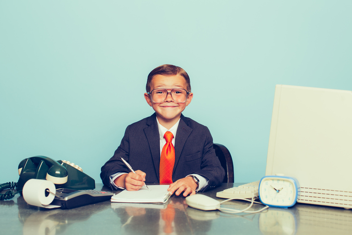 A young boy dressed as a businessman sits at his desk smiling as there is some good business happening. He sits at his desk with retro computer and phone.